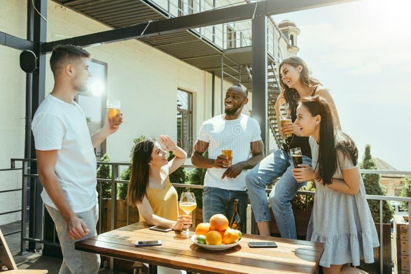 Ung grupp av vänner som dricker öl och tillsammans firar royaltyfri foto
