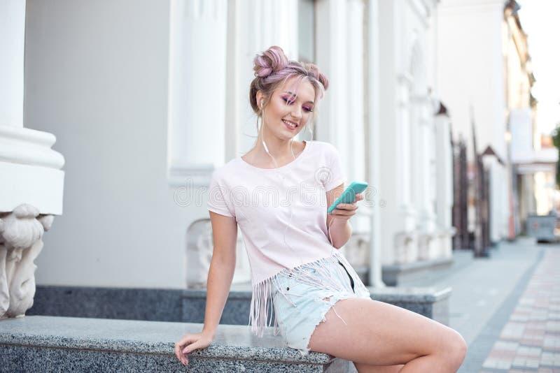 Ung gullig blondin och ljusa rosa kanter som sitter på en bänk som tar en selfie på hennes smartphone, i grov bomullstvillkortslu royaltyfri fotografi