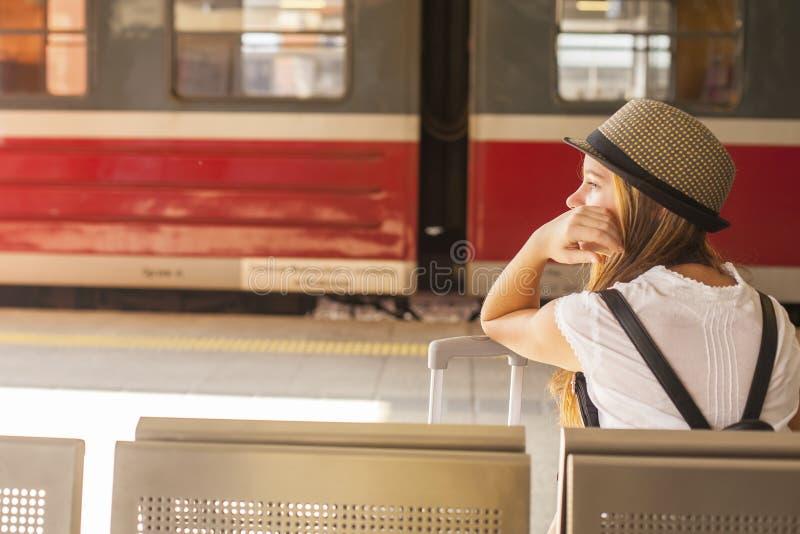 Ung gullig flicka som väntar på drevet på järnvägsstationen arkivfoto
