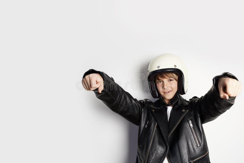 Ung gullig gladlynt tonårig pojke i svart läderomslag och den vita motohjälmen som låtsar för att rida en motorcykel över på vit arkivfoton