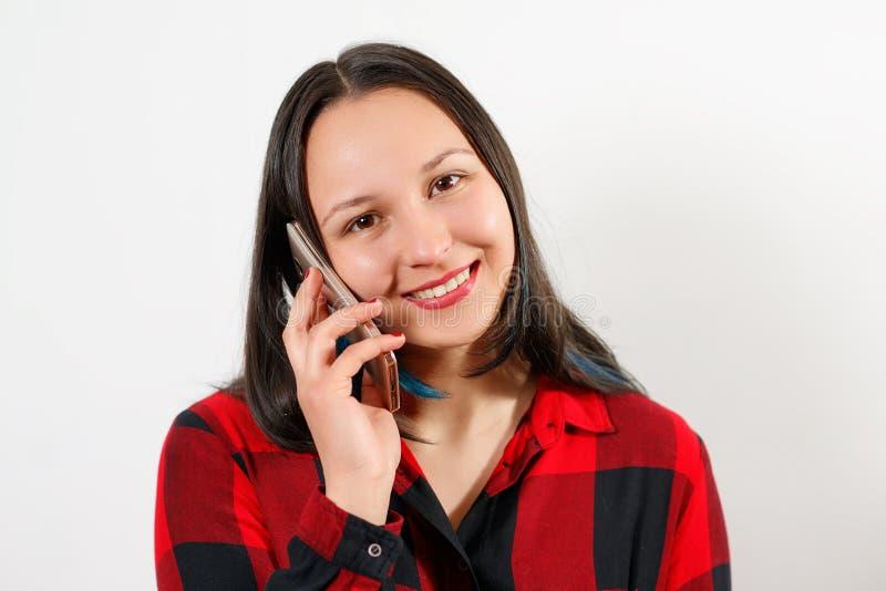 Ung gullig härlig flickakvinna i röd plädskjorta på vit bakgrund som talar på smartphonen och att le arkivfoton