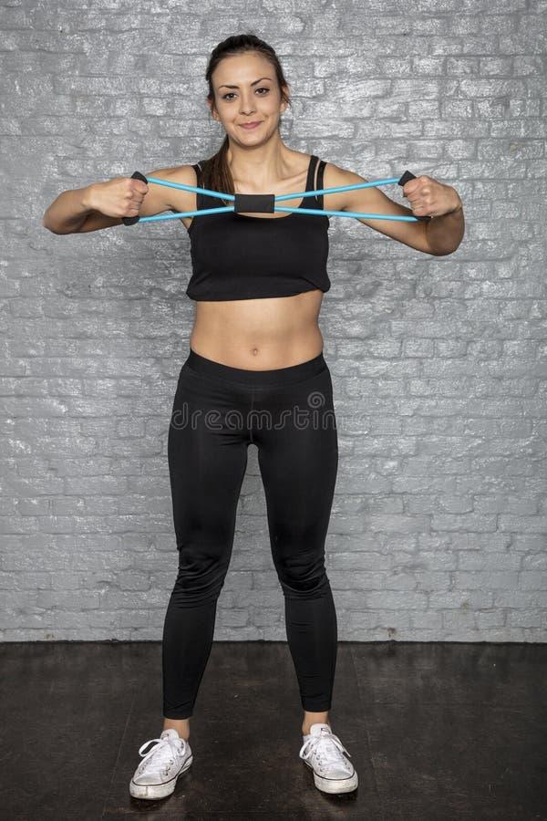 Ung gullig idrotts- kvinna som gör övningar arkivfoton