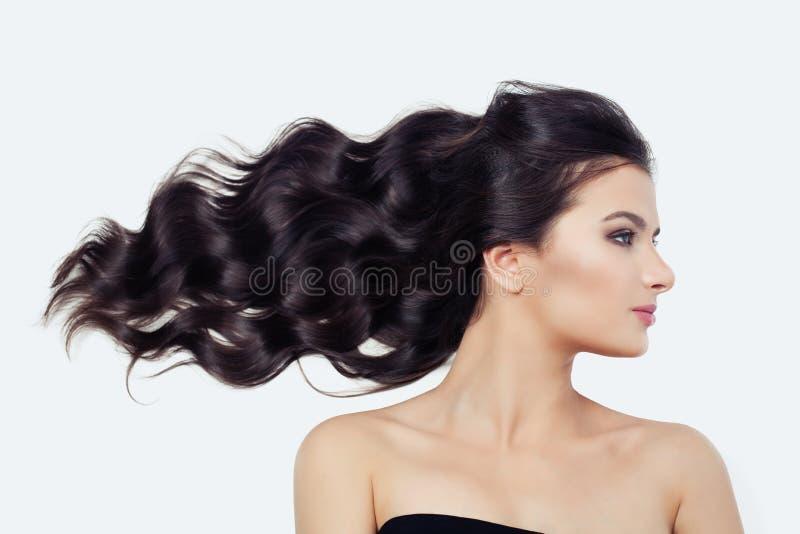 Ung gullig kvinna med att blåsa lockigt hår på vit, brunettskönhetflicka arkivfoto