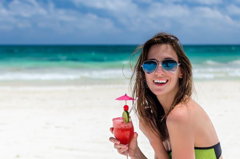 Ung gullig kvinna med den nya coctailen på den tropiska sandiga stranden fotografering för bildbyråer