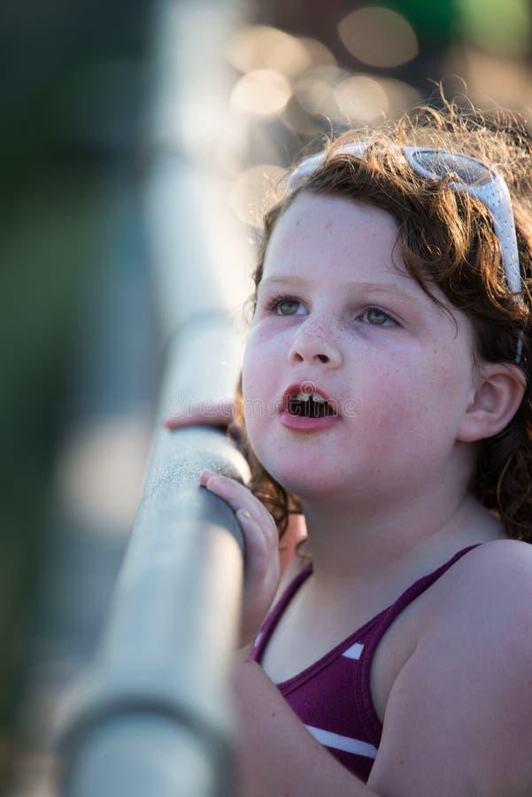 Ung gullig liten flicka på strandpromenaden som ser upp arkivfoto