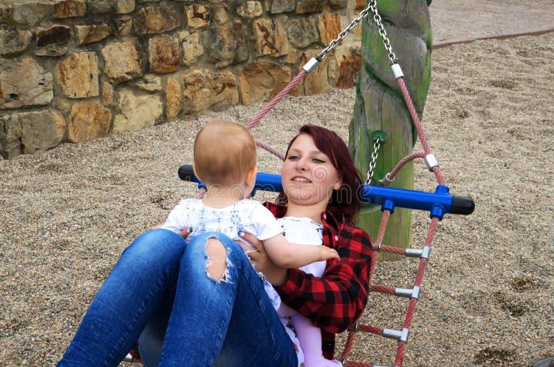 Ung gullig mamma som spelar med ett småbarn arkivbild