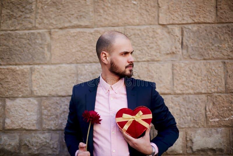 Ung gullig man som rymmer en röd blomma och gåva i form av hjärta arkivfoto