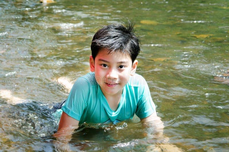 Ung gullig pojke som spelar i vattnet i en härlig flod royaltyfria bilder