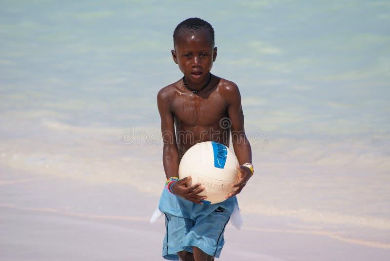 Ung gullig svart pojke i blåa kortslutningar som spelar fotboll på den soliga karibiska stranden Bavaro strand, Punta royaltyfri foto