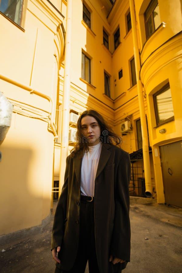 Ung gullig trendig kvinna som poserar i gården av stadshus royaltyfria foton