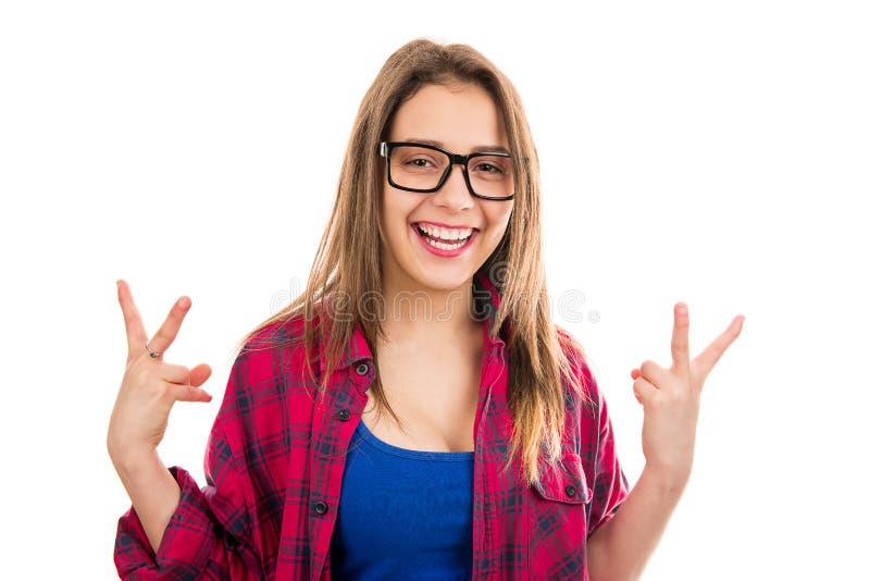 Ung gullig upphetsad kvinna i exponeringsglas som rymmer det kalla gesttecknet som firar seger arkivbild