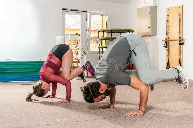 Ung härlig övning för yoga för genomkörare för akrobatkonditionpar och sträckning för långt och sunt liv, verkligt folk inget pos arkivfoto