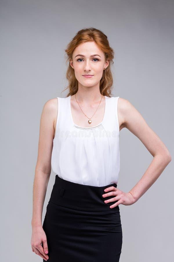Ung härlig affärskvinna för Closeupstående, student med lred lockigt hår och fräknar på framsida på grå bakgrund fotografering för bildbyråer