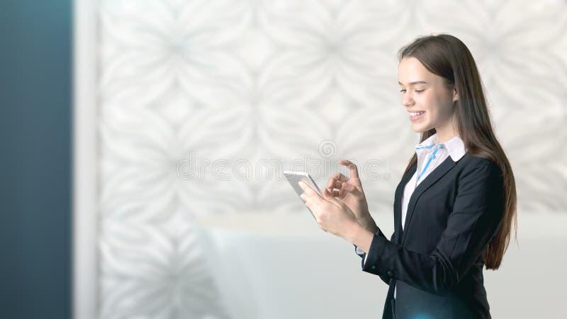 Ung härlig affärskvinna och idérikt märkes- anseende över blured inre bakgrund royaltyfri fotografi