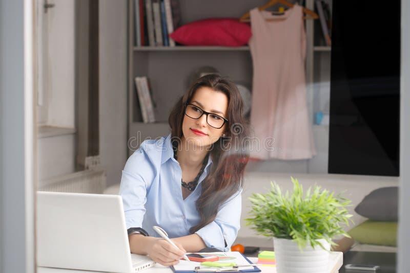 Ung härlig affärskvinna som hemma arbetar arkivbild