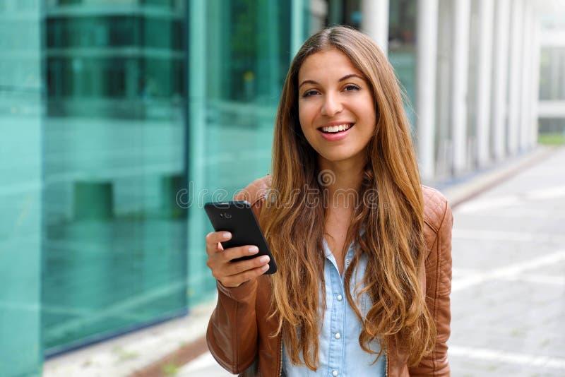 Ung härlig affärskvinna som ler och ser kameran, medan rymma mobiltelefonen i hennes hand ?gander?tt f?r home tangent f?r aff?rsi arkivbilder