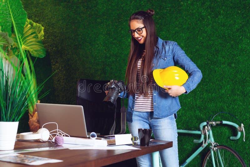 Ung härlig affärskvinna som talar på telefonen och arbetar på tabellen i ett modernt kontor - bild royaltyfria bilder