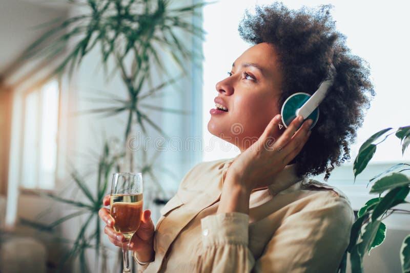 Ung härlig afrikansk amerikankvinna som kopplar av och lyssnar till musik genom att använda headphonen fotografering för bildbyråer