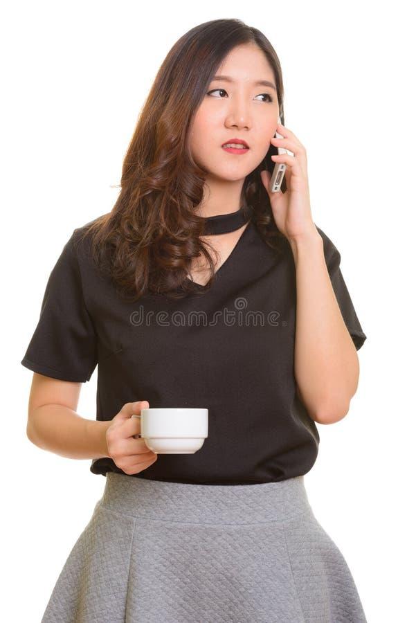 Ung härlig asiatisk affärskvinna som talar på mobiltelefonwhil royaltyfria foton