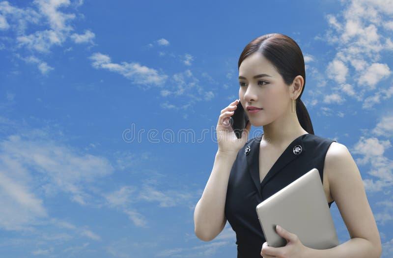 Ung härlig asiatisk affärskvinna som talar på smart mobil phon royaltyfri bild
