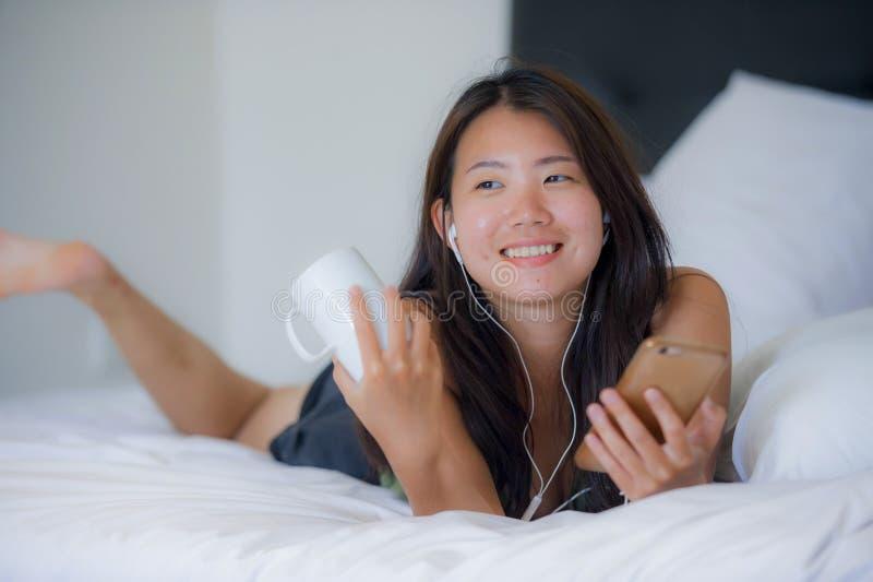 Ung härlig asiatisk kinesisk kvinna med skalmen som lyssnar till musik som ler lyckligt ligga på säng genom att använda internet  fotografering för bildbyråer