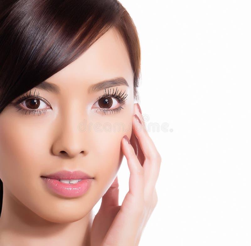 Ung härlig asiatisk kvinna med prickfri hud och perfekt smink- och brunthår fotografering för bildbyråer