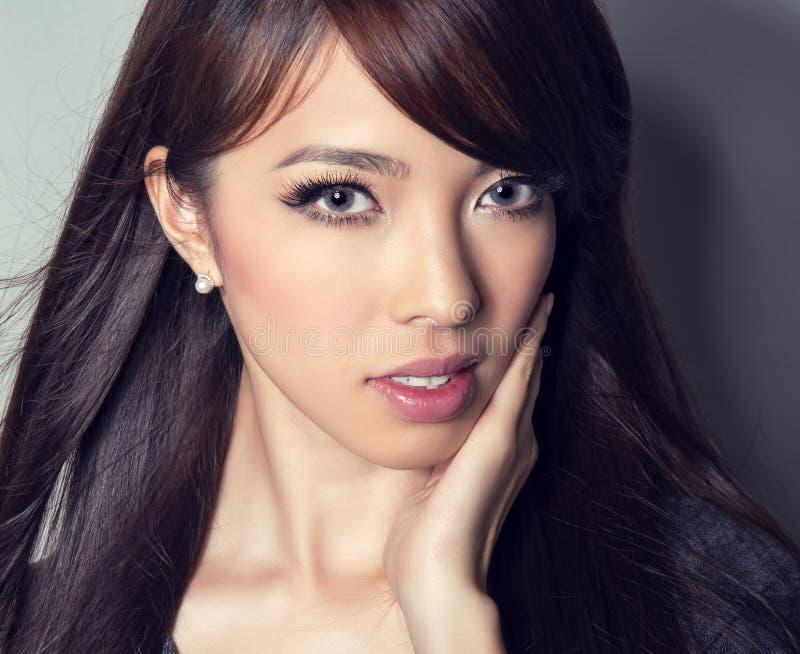 Ung härlig asiatisk kvinna med prickfri hud och perfekt smink- och brunthår arkivbild
