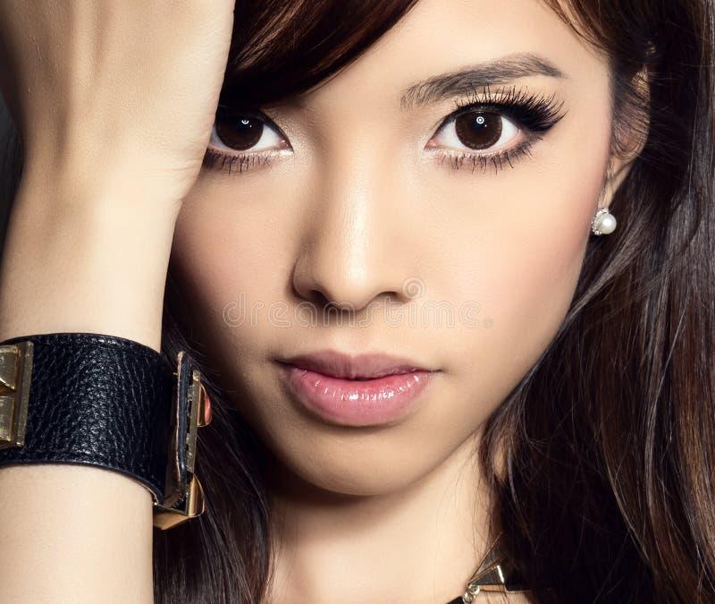 Ung härlig asiatisk kvinna med prickfri hud och perfekt smink- och brunthår arkivbilder