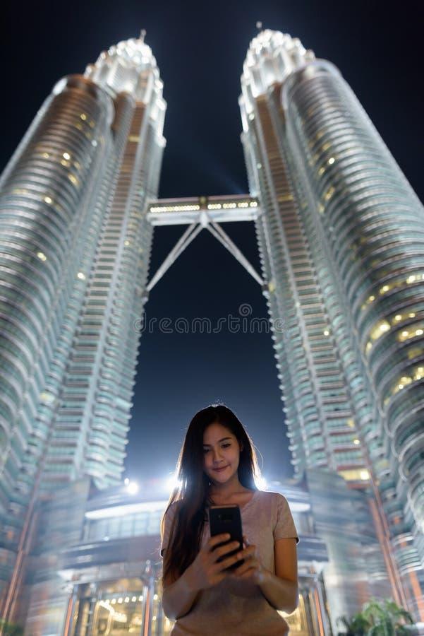 Ung härlig asiatisk kvinna mot sikten för låg vinkel av Petronen arkivfoto