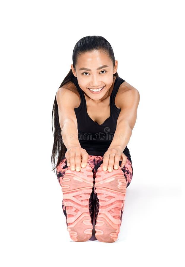 Ung härlig asiatisk kvinna som gör sträcka kroppen och ben royaltyfria foton