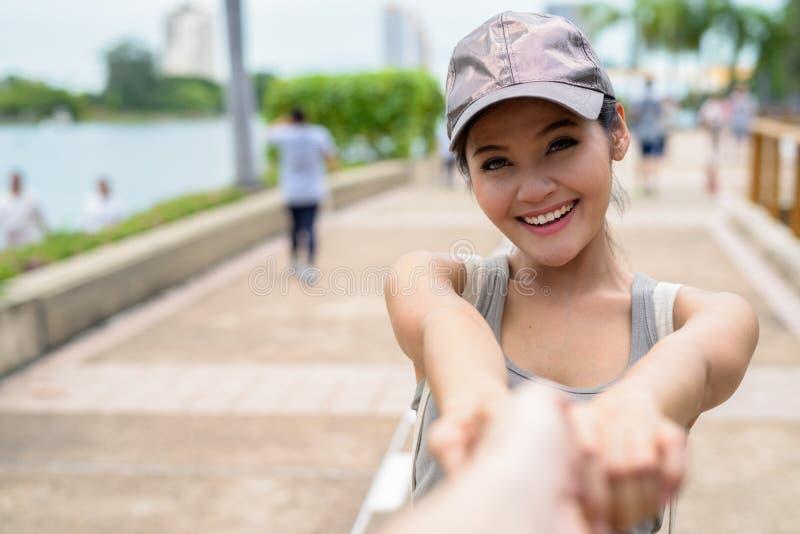 Ung härlig asiatisk kvinna som kopplar av på parkera fotografering för bildbyråer