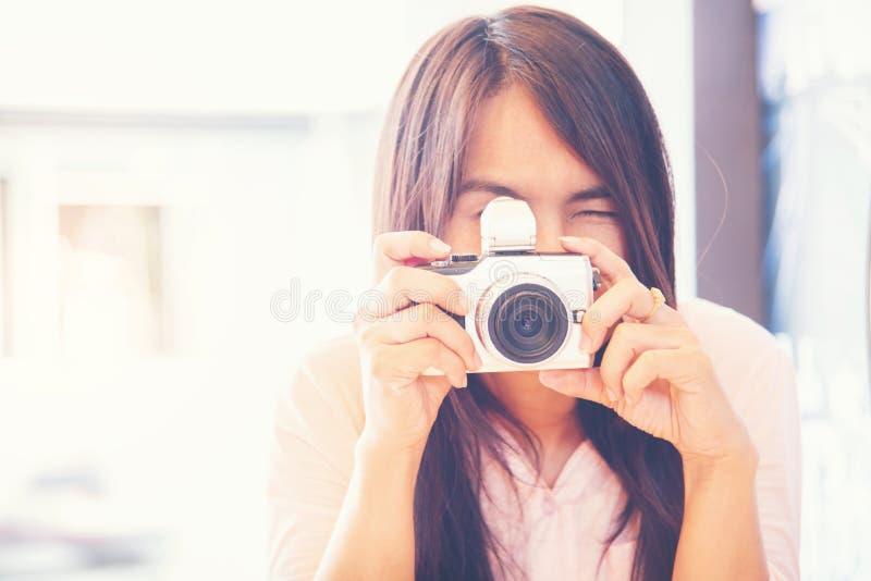 Ung härlig asiatisk kvinna som utomhus tar fotoet med DSLR-digi arkivfoto