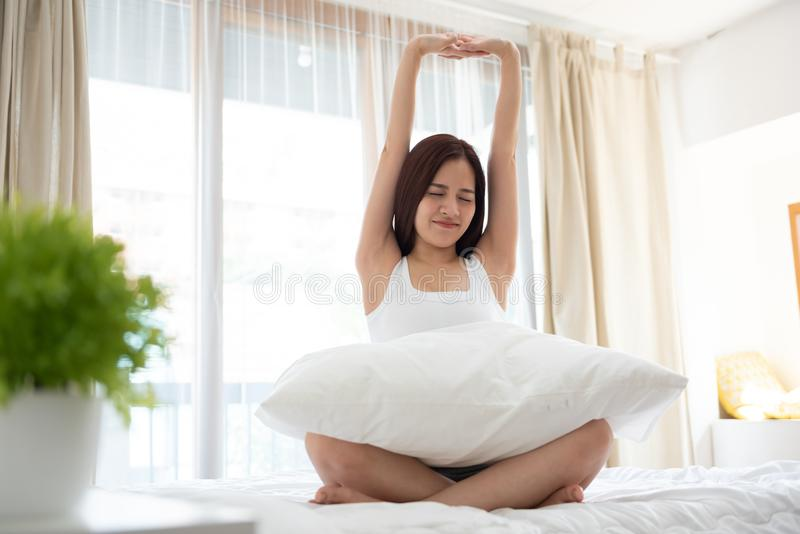 Ung härlig asiatisk kvinna som vaknar upp i hennes säng royaltyfri bild