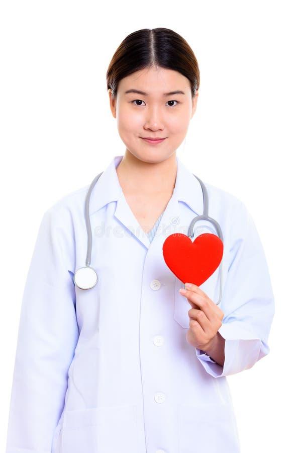 Ung härlig asiatisk kvinnadoktor som rymmer röd hjärta arkivfoto