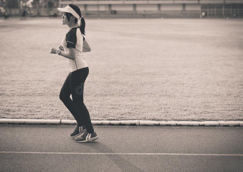 Ung härlig asiatisk kvinnalöpare som kör på spår under solnedgången, tonat svartvitt fotografering för bildbyråer