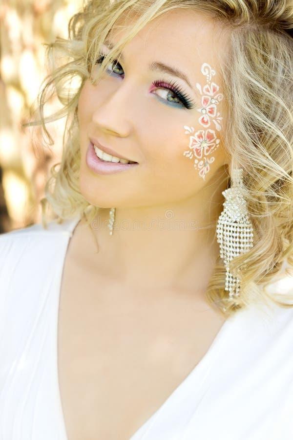 Ung härlig attraktiv flickablondin med långt hår i en solig dag c blåa ögon för en makeup i en vit klänning med en leendenolla arkivbilder