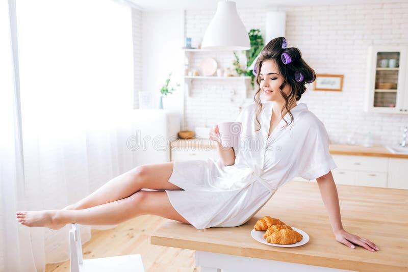 Ung härlig bekymmerslös kvinna att sitta och vila på tabellen i kök Morgon Brunett med hårrullar i hårdrinkte eller arkivfoto