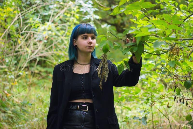 Ung härlig blå haired flicka i svarta kläder som går i skog royaltyfri foto