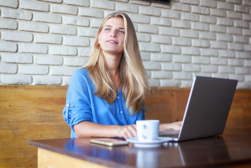 Ung härlig blond flicka 20 år som arbetar med bärbara datorn i kafé Online-affär för modern freelancer royaltyfri bild
