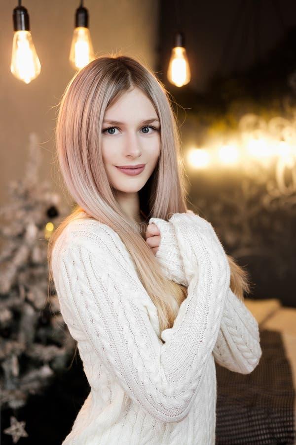 Ung härlig blond flicka i en varm vit stucken tröja på bakgrunden av ett enkelt hemtrevligt rum med jul arkivbild