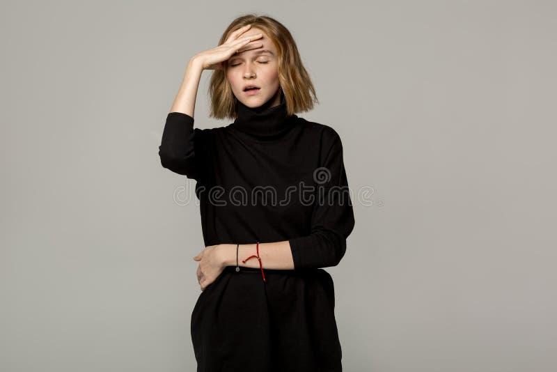 Ung härlig blond flicka med huvudvärk, bärande svart klänning fotografering för bildbyråer