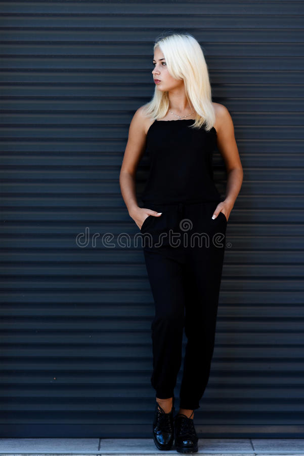 Ung härlig blond flicka som poserar på bakgrunden av det stads- landskapet Sexig dam i en svart klänning med ett angenämt utseend arkivbild