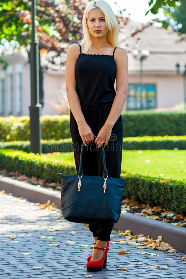 Ung härlig blond flicka som poserar på bakgrunden av det stads- landskapet Sexig dam i en svart klänning och röda skor royaltyfria foton
