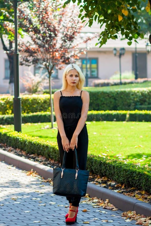 Ung härlig blond flicka som poserar på bakgrunden av det stads- landskapet Sexig dam i en svart klänning och röda skor arkivbilder