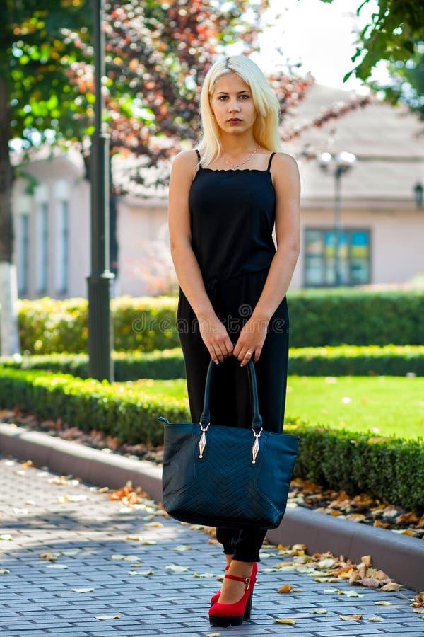 Ung härlig blond flicka som poserar på bakgrunden av det stads- landskapet Sexig dam i en svart klänning och röda skor arkivbild