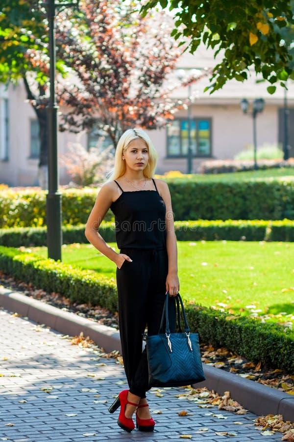 Ung härlig blond flicka som poserar på bakgrunden av det stads- landskapet Sexig dam i en svart klänning och röda skor med vädjan arkivfoton