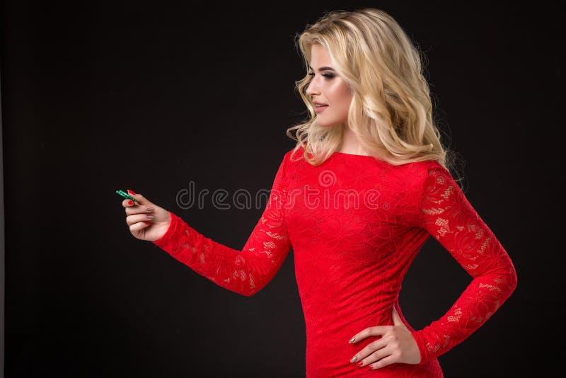 Ung härlig blond kvinna med pokerchiper över svart poker arkivfoton