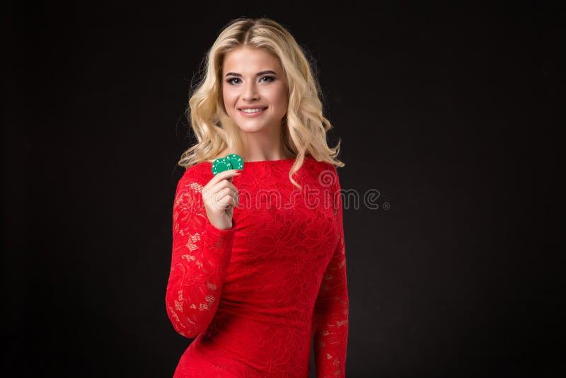 Ung härlig blond kvinna med pokerchiper över svart poker arkivbilder