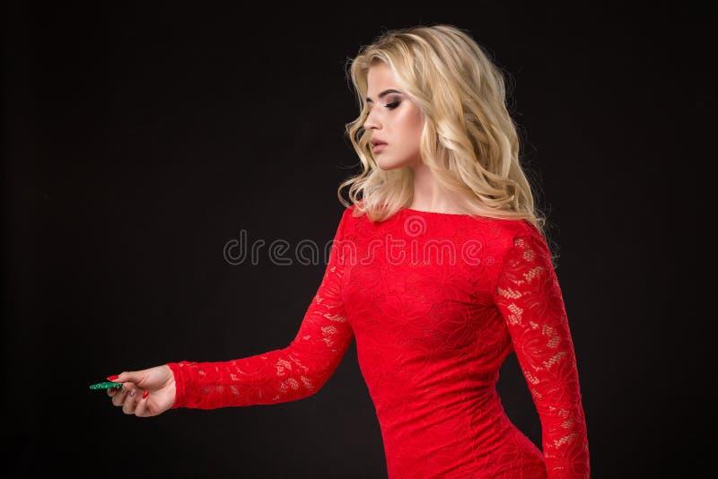 Ung härlig blond kvinna med pokerchiper över svart poker arkivfoto