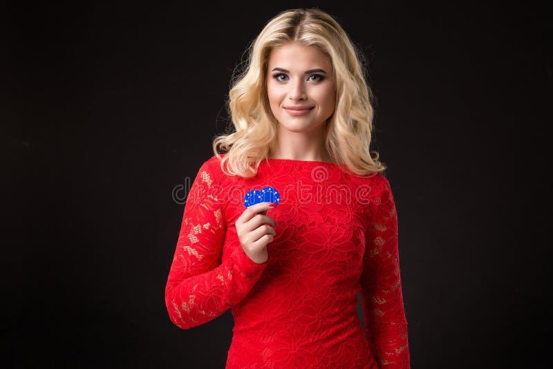 Ung härlig blond kvinna med pokerchiper över svart poker royaltyfri fotografi